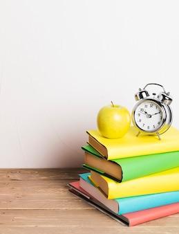 Relógio despertador e maçã amarela na pilha de livros didáticos