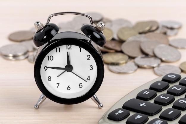 Relógio despertador e moedas com calculadora