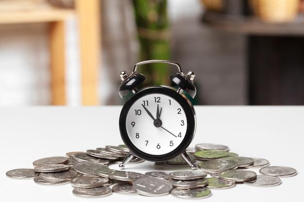Relógio despertador e moedas de dinheiro em cima da mesa.