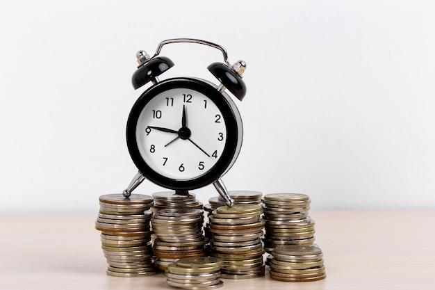 Relógio despertador e moedas em branco