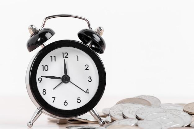 Relógio despertador e moedas na superfície branca