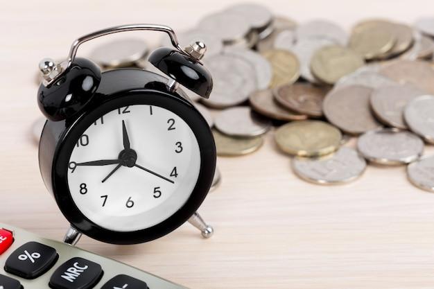 Relógio despertador e moedas