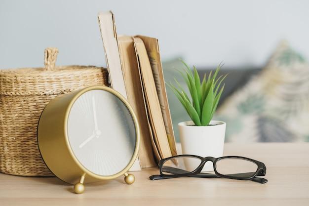 Relógio despertador e objetos de papelaria de escritório na mesa de madeira