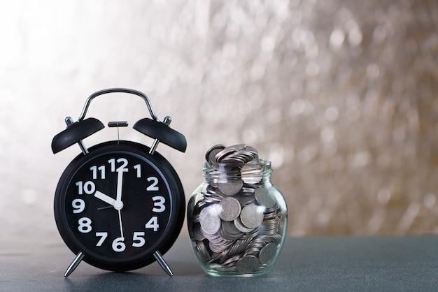 Relógio despertador e passo de pilhas de moedas com moedas em frasco de vidro