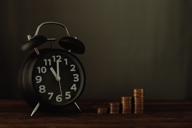 Relógio despertador e passo de pilhas de moedas na mesa de trabalho