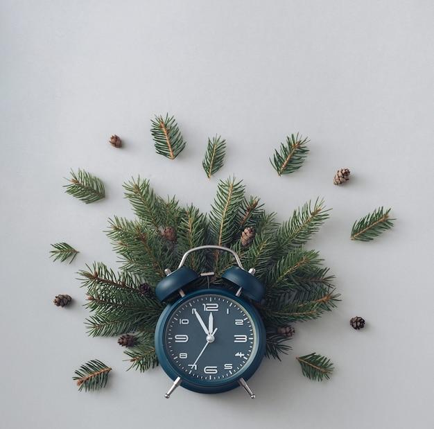 Relógio despertador e ramos de pinheiro em um conceito de fundo cinza de férias de inverno e férias flat lay