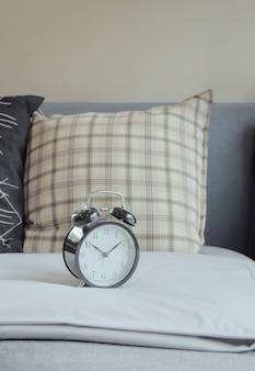 Relógio despertador e travesseiros padrão gráfico na cama