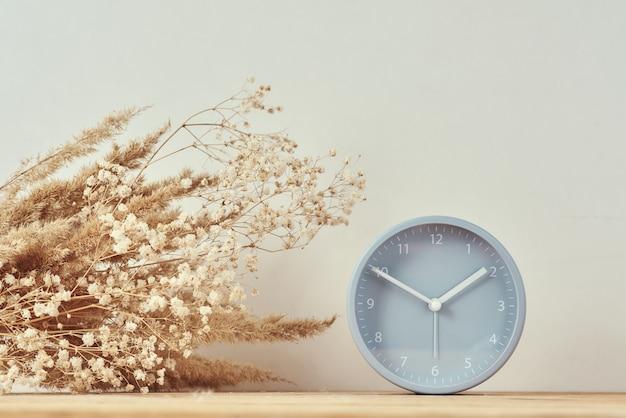 Relógio despertador e vaso caseiro com planta seca na mesa de madeira