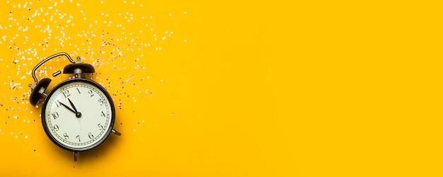 Relógio despertador em um fundo de banner amarelo com glitter festivo. conceito de fundo mínimo de véspera de ano novo.