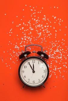 Relógio despertador em um fundo vermelho com glitter festivo. conceito de fundo mínimo de véspera de ano novo.