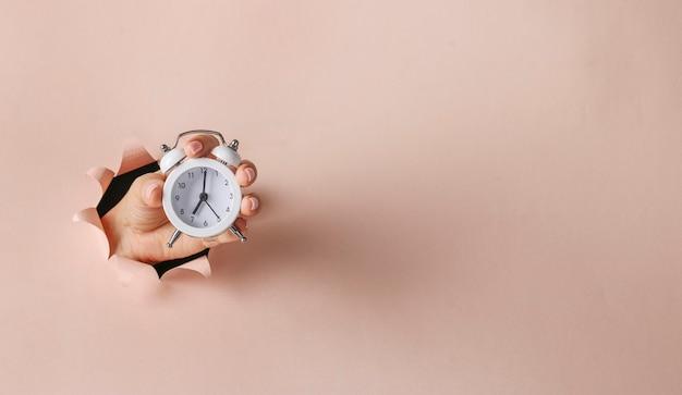 Relógio despertador em uma mão feminina segurando através de um buraco redondo em papel rosa. hora do café da manhã bom dia, copie espaço