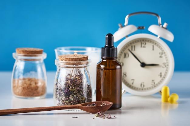 Relógio despertador, ervas medicinais e óleo de aromaterapia sobre fundo azul