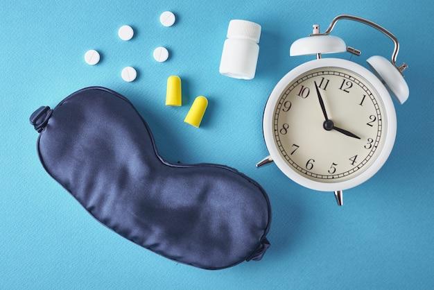 Relógio despertador, máscara para dormir, tampões para os ouvidos e pílulas sobre fundo azul