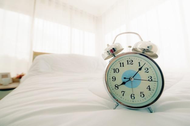 Relógio despertador na cama no quarto pela manhã com luz solar.