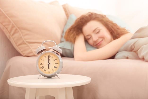 Relógio despertador na mesa no quarto de uma mulher bonita.
