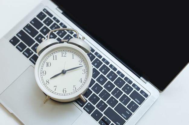 Relógio despertador no computador portátil na mesa. tempo de negócios trabalhando no espaço de trabalho.