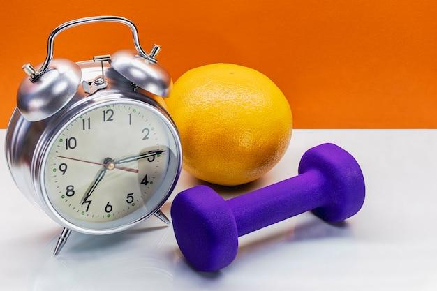 Relógio despertador no fundo de halteres. concepção de esportes e estilo de vida saudável.
