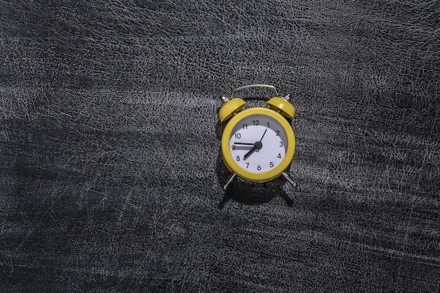 Relógio despertador no quadro de giz escolar. de volta à escola