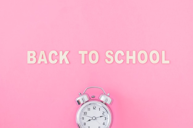 Relógio despertador perto de volta à escola escrevendo
