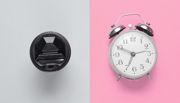 Relógio despertador, recipiente com café no fundo cinza rosa. vista do topo