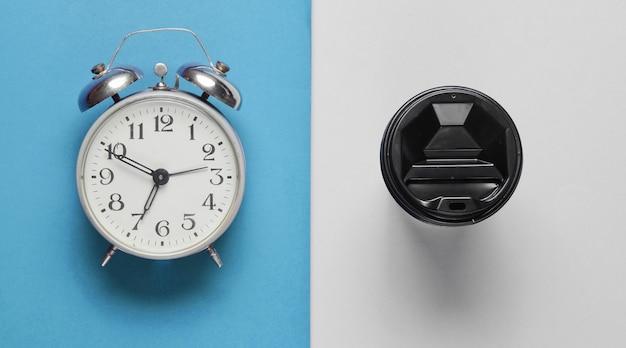 Relógio despertador, recipiente com café sobre fundo cinza azul. vista do topo