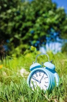 Relógio despertador, relógio azul sobre fundo verde grama