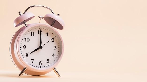 Relógio despertador vintage mostrando 8'o hora do relógio contra fundo bege