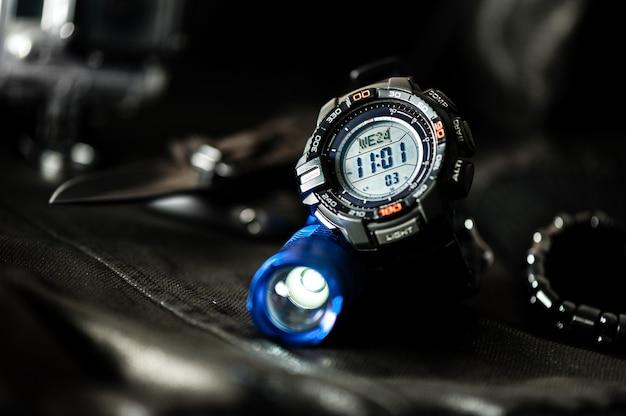Relógio digital preto para atividades ao ar livre com recurso de cronômetro, cronômetro, luz de fundo e resistência à água.