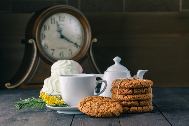 Relógio e café da manhã na mesa de madeira escura