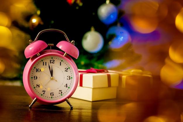 Relógio e caixas de presente perto da árvore de natal na véspera de ano novo_