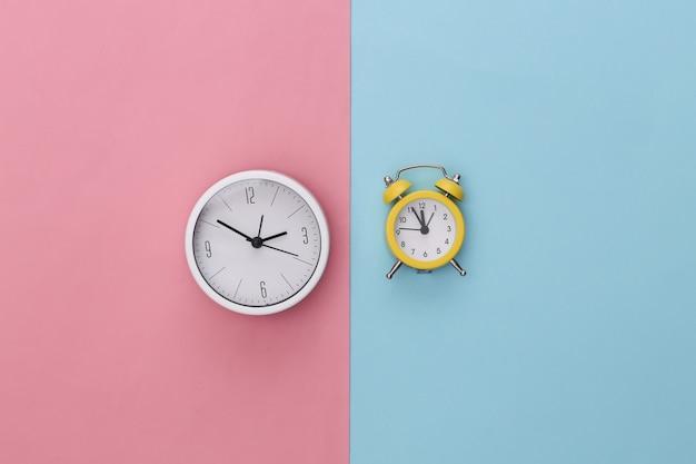 Relógio e despertador em fundo rosa pastel azul.