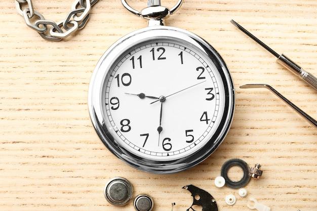 Relógio e ferramentas para reparo em fundo de madeira