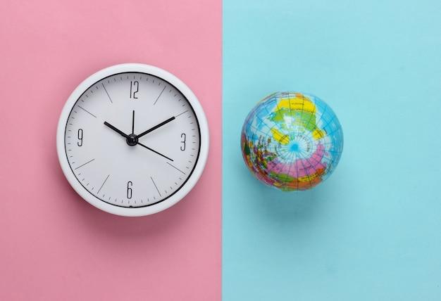 Relógio e globo em fundo rosa pastel azul. hora mundial. vista do topo