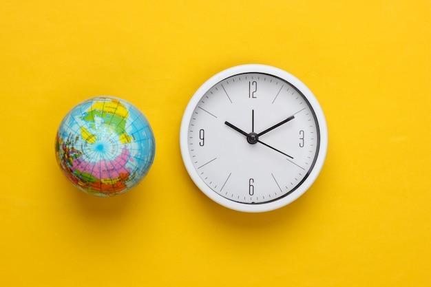 Relógio e globo em um fundo amarelo. hora mundial. vista do topo