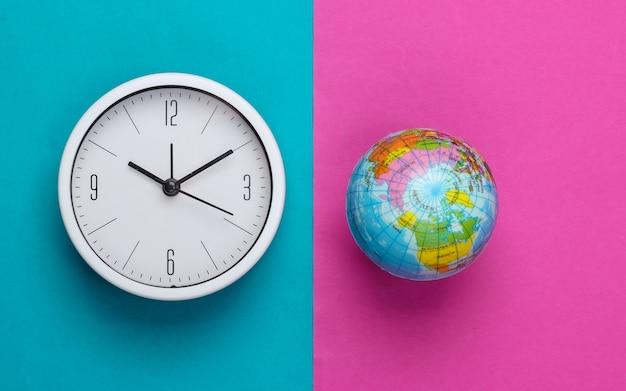 Relógio e globo sobre fundo rosa azul. hora mundial. vista do topo