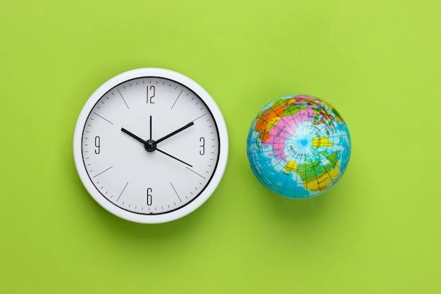 Relógio e globo sobre um fundo verde. hora mundial. vista do topo