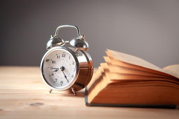 Relógio e livro na mesa