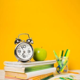 Relógio e livros com fundo desfocado