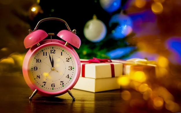 Relógio e presentes antes da árvore de natal à meia-noite_