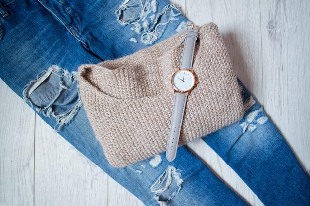 Relógio elegante em um suéter e jeans rasgados
