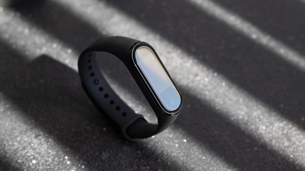 Relógio eletrônico preto e rastreador de aptidão inteligente na superfície preta texturizada