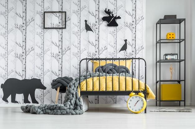 Relógio em forma de cervo preto pendurado na parede da sala com papel de parede de árvores da floresta