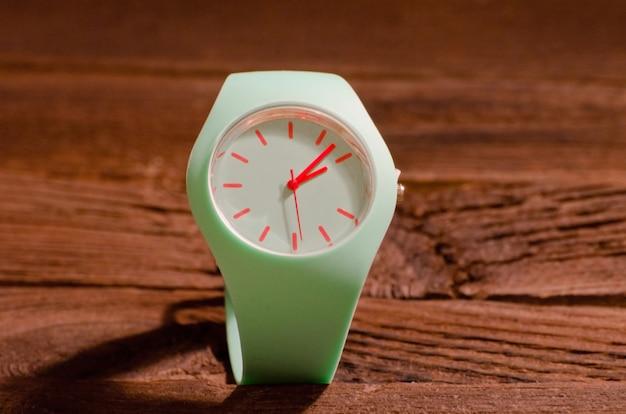 Relógio esporte verde na superfície de madeira