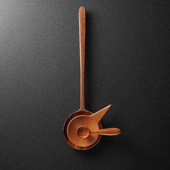 Relógio feito de colheres de madeira em um fundo preto de concreto