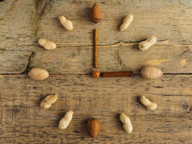 Relógio feito de diferentes nozes e canela na mesa de madeira