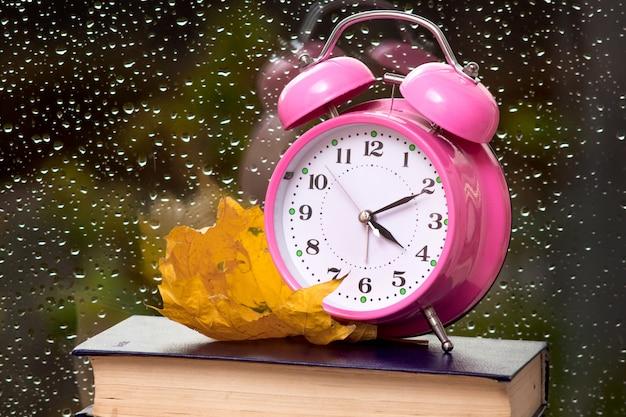 Relógio, folhas secas de outono e livros sobre o fundo de um vidro de janela molhado