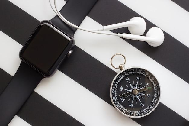 Relógio, fones de ouvido e bússola sobre um fundo preto e branco