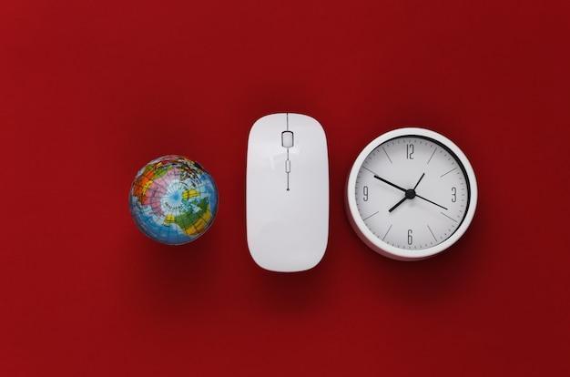 Relógio, globo com o mouse do pc sobre fundo vermelho. prazo de trabalho. vista do topo.