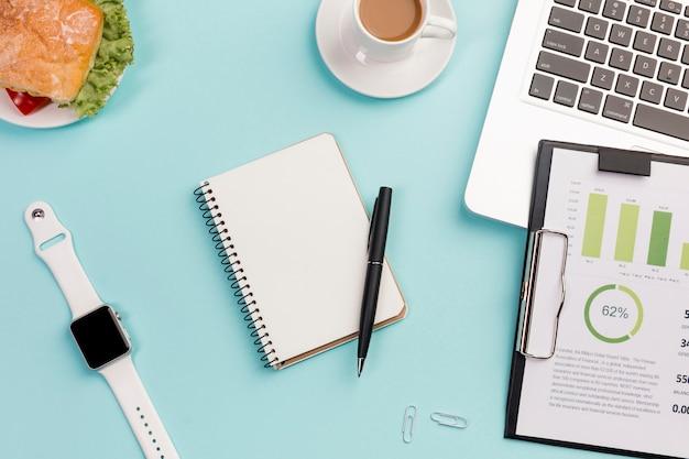 Relógio inteligente branco, artigos de papelaria, sanduíche, prancheta com plano de orçamento e laptop na mesa de escritório azul