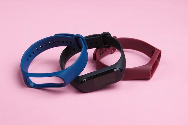 Relógio inteligente com pulseiras intercambiáveis em fundo rosa. rastreador de fitness. gadgets modernos